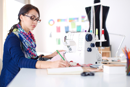 sewing machines: Young woman sewing while sitting at her working place .