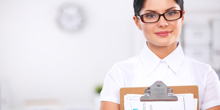 Portrait of a young woman working at office standing with folder Stock Photo