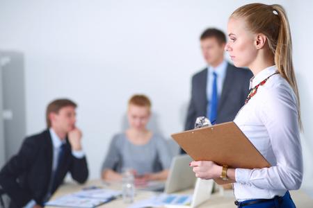 フォルダーとオフィスの地位で働く若い女性の肖像画。若い女性の肖像画。ビジネス女性