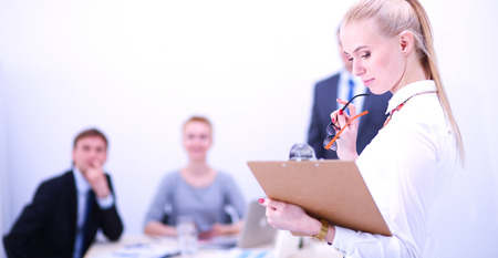 Portrait of a young woman working at office standing with folder . Portrait of a young woman. Business woman