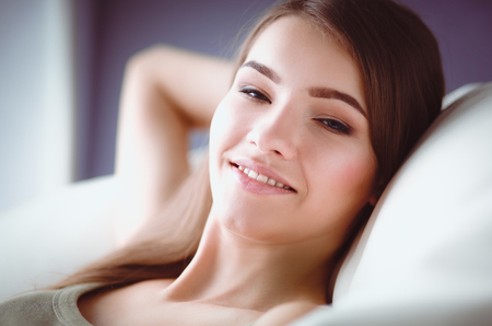 doze: Closeup of a smiling young woman lying on couch Stock Photo