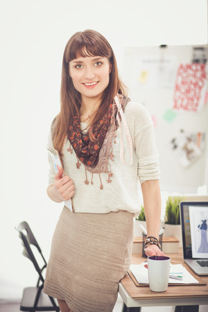 Portrait of attractive female fashion designer standing at office Stock Photo