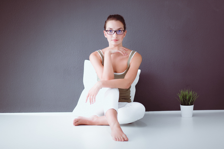 Attractive caucasian girl sitting on floor with cup and tablet near wall Stock Photo