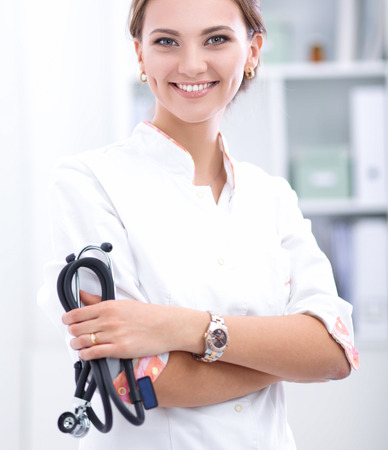 Young woman doctor standing at hospital with medical stethoscope