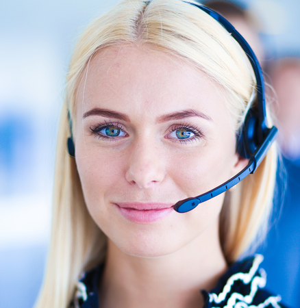 Businesswoman with headset smiling at camera in call center. Businessmen in headsets on background Stock Photo