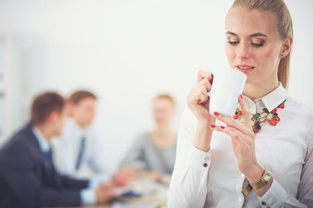 立っているオフィスで働く若い女性の肖像画。若い女性