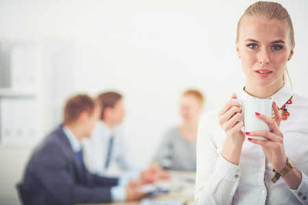 Portrait of a young woman working at office standing . Young woman