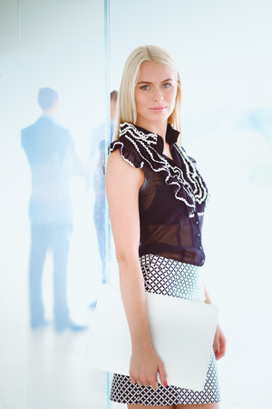 Young businesswoman holding a laptop, standing on office . Stock Photo