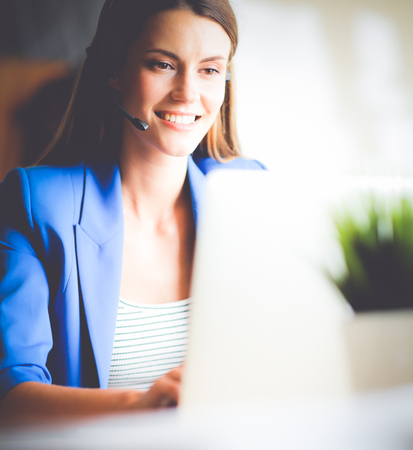ヘッドセットとラップトップで自分の机で働いて美しい女性の肖像画。 写真素材