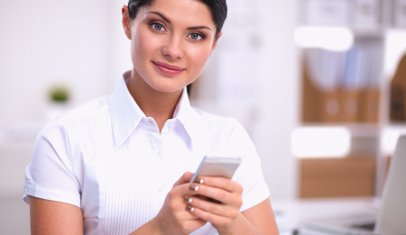 Businesswoman sending message with smartphone sitting in the office