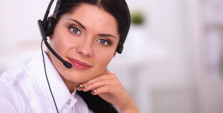 Portrait of beautiful businesswoman working at her desk with headset and laptop Stock Photo
