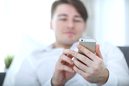 Handsome young man using smartphone at home
