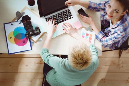 Fotografo femminile che si siede sulla scrivania con il computer portatile. Fotografo femminile