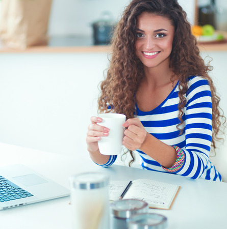 Smiling young woman with laptop in the kitchen at home