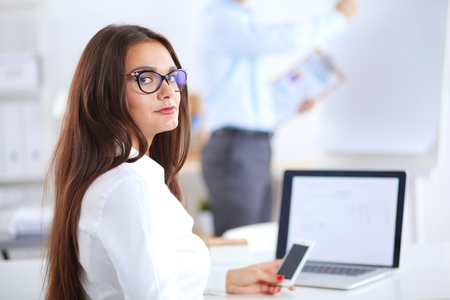 Attractive businesswoman sitting in the office, at the desk. Attractive businesswoman
