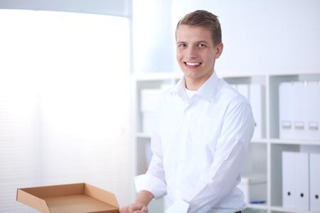 회색 배경에 앉아 웃 고 젊은 남자의 초상화. 젊은 남자의 초상