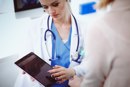 Doctor and patient discussing something while sitting at the table . Medicine and health care concept. Doctor and patient.