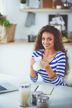 Smiling young woman with coffee cup and laptop in the kitchen at home. Smiling young woman Stock Photo