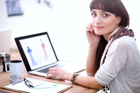 Portrait of attractive female fashion designer sitting at office desk. Female fashion designer