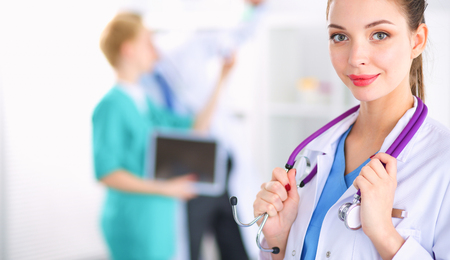 Woman doctor standing with stethoscope at hospital Banco de Imagens