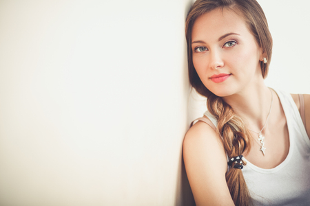 Young woman sitting on the floor near wall . Young woman