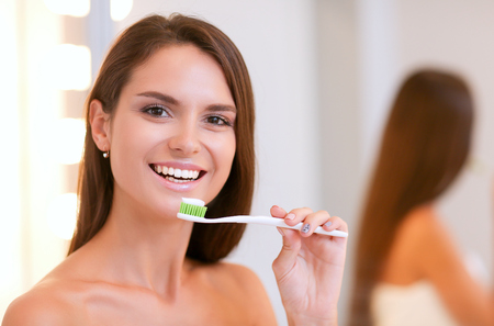 Portrait of a young girl cleaning her teeth Фото со стока