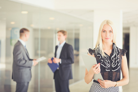 Portrait of young businesswoman in office with colleagues in the background .