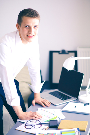 Young business man working in office ,standing . Young business man