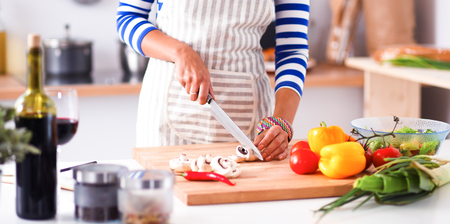 Young woman cutting vegetables in kitchen Stok Fotoğraf