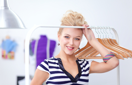 Beautiful young stylist woman near rack with hangers Stock Photo