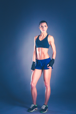 Muscular young woman posing in sportswear against black background. Imagens