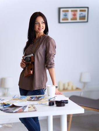 Young woman watching footage on film, standing near window Stock Photo