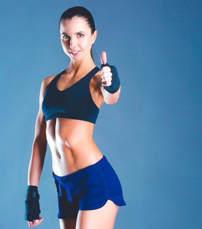 Portrait of a happy fitness woman showing ok sign Imagens