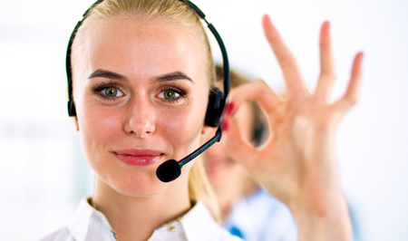 Smiling customer service girl showing ok, isolated on white background.