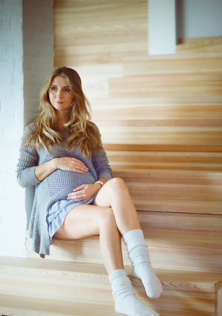 Beautiful young pregnant woman sits on the steps of a wooden ladder
