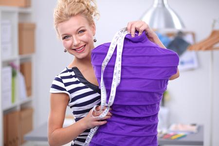 Smiling fashion designer woman standing near mannequin in office Reklamní fotografie