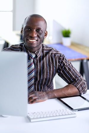 Handsome afro american businessman in classic suit is using a laptop and smiling while working in office