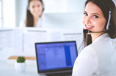 Uśmiechnięta bizneswoman lub operator infolinii z zestawem słuchawkowym i komputerem w biurze