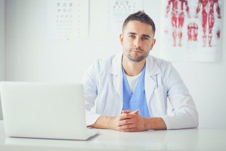 Portret van een mannelijke arts met laptop zittend aan een bureau in medisch kantoor.