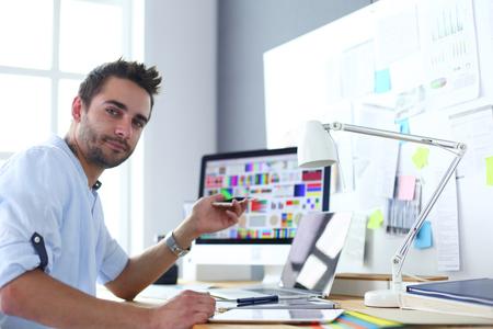 Ritratto di giovane designer seduto allo studio grafico davanti a laptop e computer mentre si lavora online. Archivio Fotografico