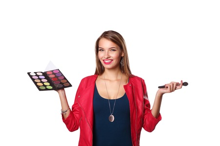 Young beautiful woman holds in one hand and a palette with paint and shadows for makeup, second hand brush for makeup. 版權商用圖片