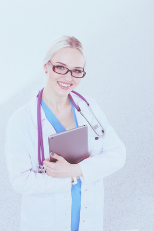 Female doctor using a digital tablet and standing on white background.