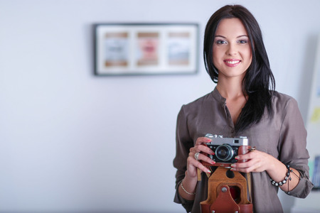 Portrait of smiling young woman with camera in loft apartment