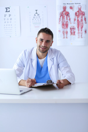 Portrait of a male doctor with laptop sitting at desk in medical office. Stok Fotoğraf