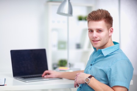 Young businessman working in office, sitting at desk Banco de Imagens