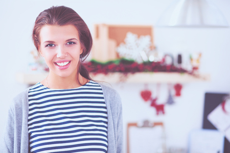 Portrait of young woman against kitchen interior background Stock Photo