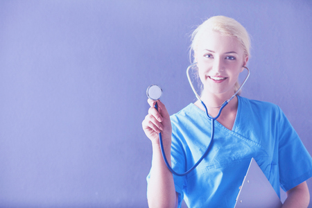 Female doctor with a stethoscope listening, isolated on gray background Stock Photo