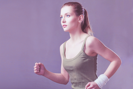 running caucasian woman studio isolated on gray background