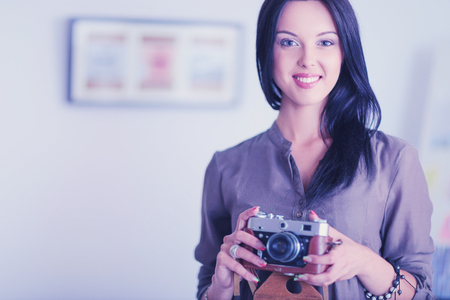 Portrait of smiling young woman with camera sitting in loft apartment