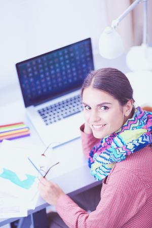 Beautiful fashion designer sitting at the desk in studio Stock Photo